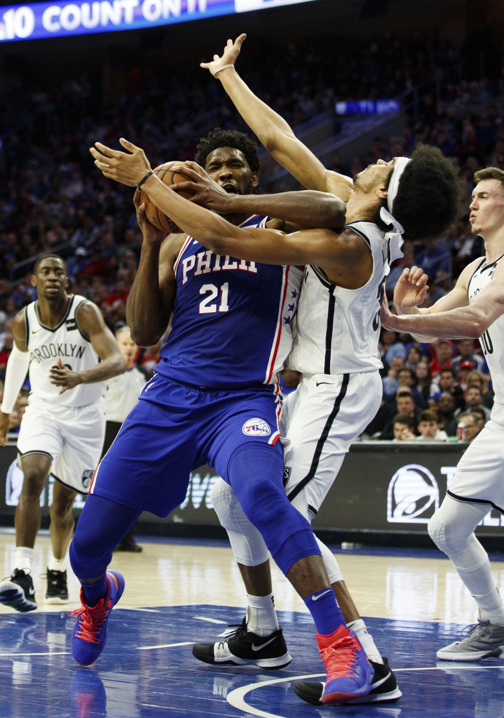 Philadelphia 76ers' Joel Embiid, left, of Cameroon, with the flaguant 1 foul on Brooklyn Nets' Jarrett Allen, right, as he was going for the shot duri...