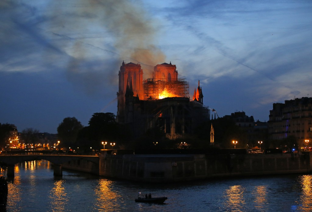Firefighters tackle the blaze as flames and smoke rise from Notre Dame cathedral as it burns in Paris, Monday, April 15, 2019. Massive plumes of yello...
