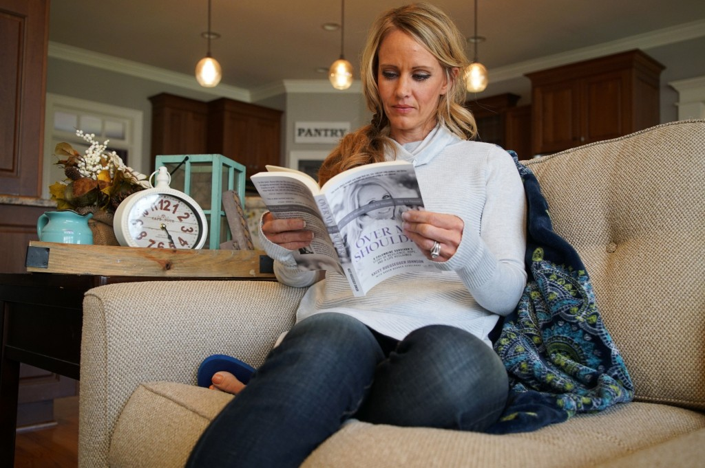 """In this Wednesday, March 27, 2019, photo, Kacey Ruegsegger Johnson pages through a copy of her memoir at her home in Cary, N.C. The book, """"Over My Sho"""