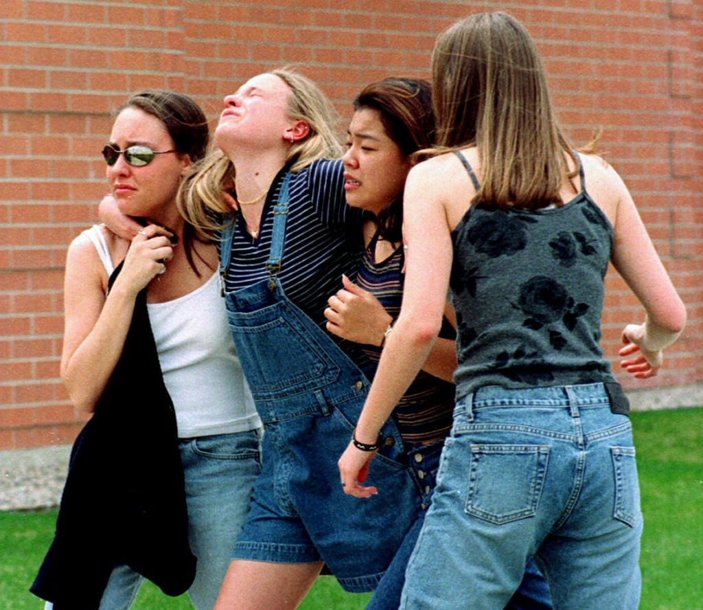 FILE - In this April 20, 1999, file photo, women head to a library near Columbine High School where students and faculty members were evacuated after