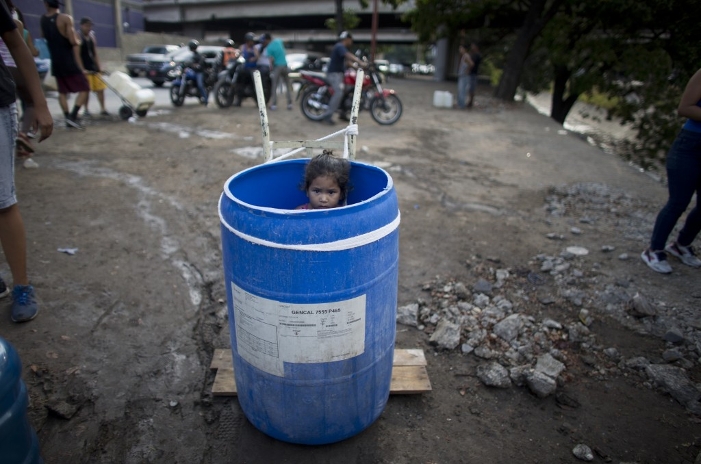 FILE - In this March 11, 2019 file photo, a little girl stands inside a plastic barrel while her family waits to collect water from an open pipe above