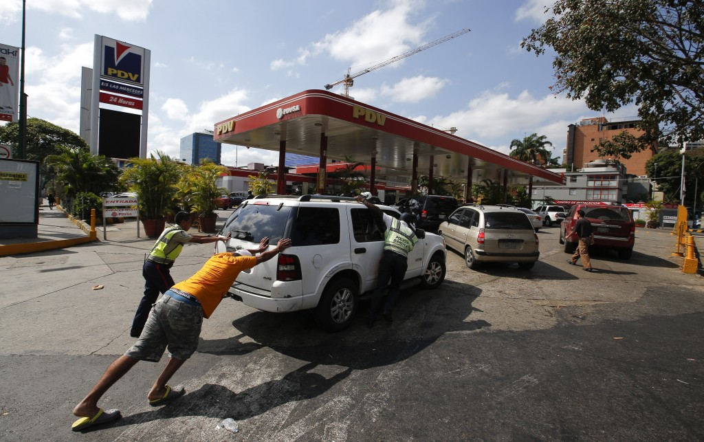 FILE - In this March 10, 2019 file photo, people push a car without fuel to one of the few gas stations that has its own electric generator during an