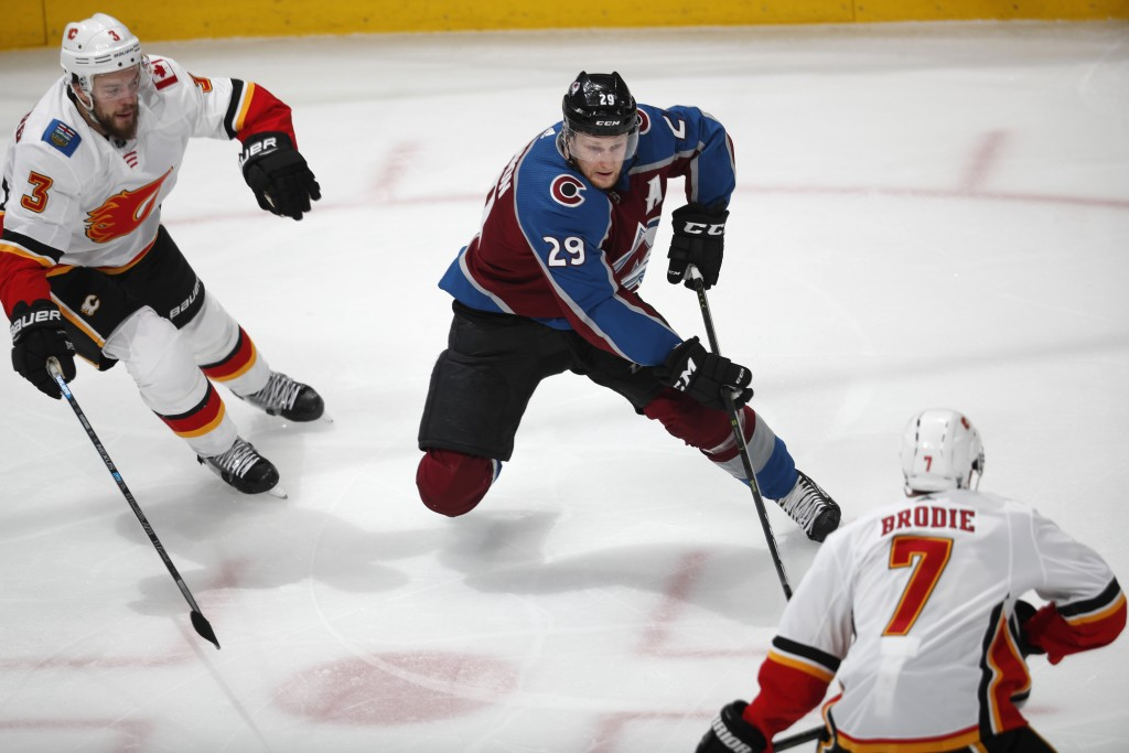 Colorado Avalanche center Nathan MacKinnon, center, drives to the net between Calgary Flames defensemen Oscar Fantenberg, left, and TJ Brodie in the f