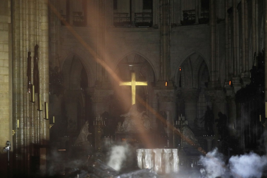 Smoke is seen around the alter inside Notre Dame cathedral in Paris, Monday, April 15, 2019. A catastrophic fire engulfed the upper reaches of Paris'