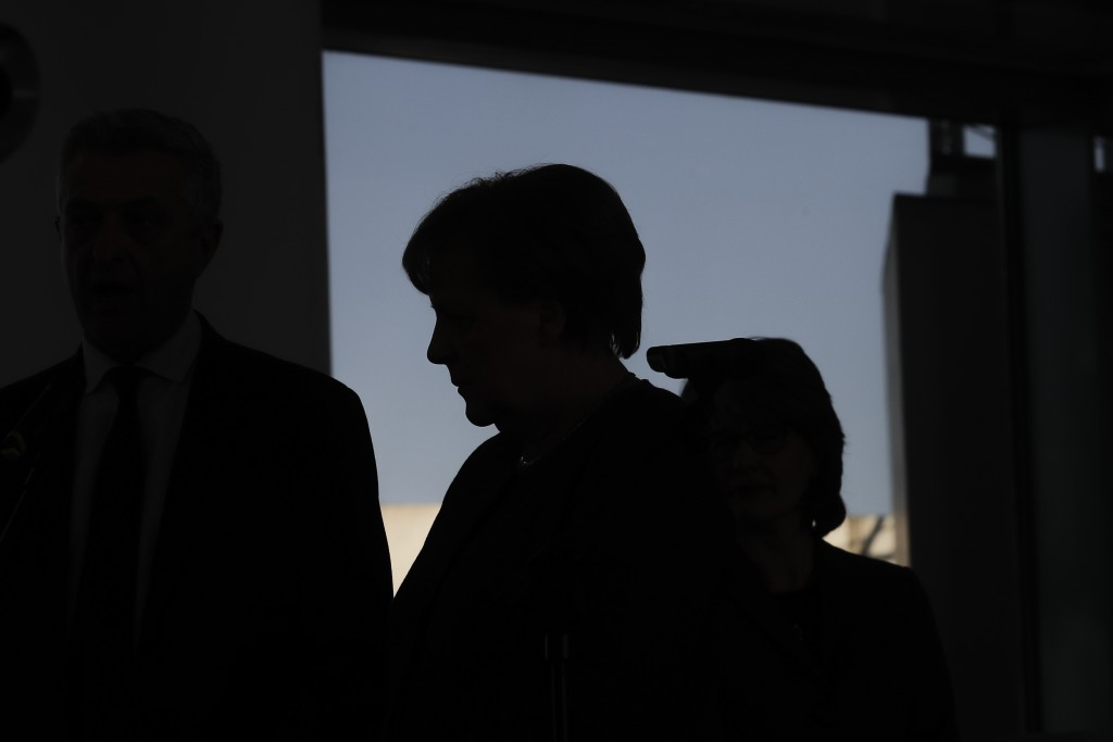 German Chancellor Angela Merkel silhouette in front of a window as she welcomes United Nations High Commissioner for Refugees Filippo Grandi for a mee