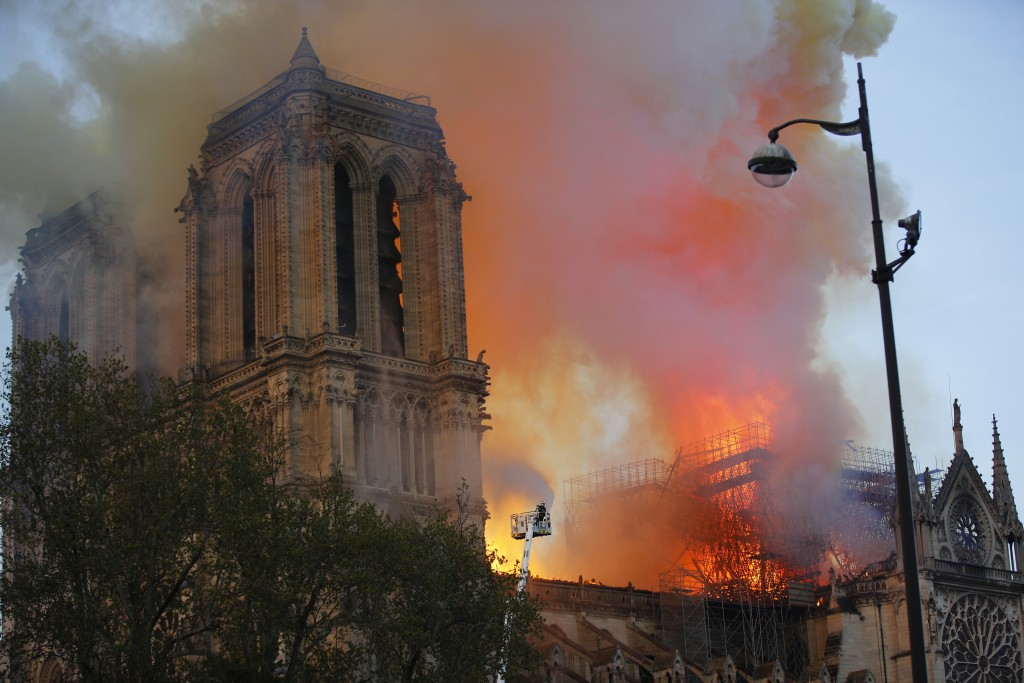 Firefighters use hoses as Notre Dame cathedral burns in Paris, Monday, April 15, 2019. A catastrophic fire engulfed the upper reaches of Paris' soarin