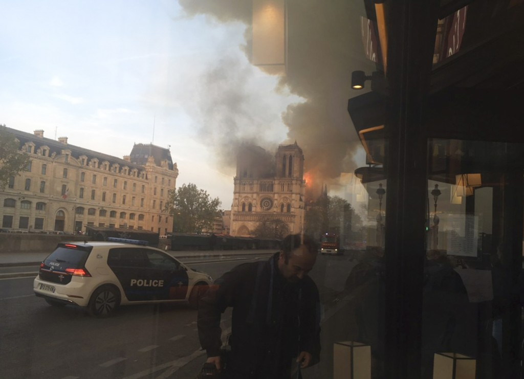 In this photo taken from inside a cafe, a police car patrol while Notre Dame cathedral isburning in Paris, Monday, April 15, 2019. A massive fire engu