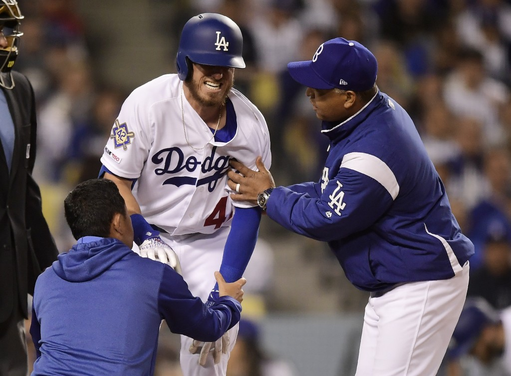 Los Angeles Dodgers' Cody Bellinger, center, winces after being hit in the knee by a pitch as a trainer and manager Dave Roberts tend to him during th