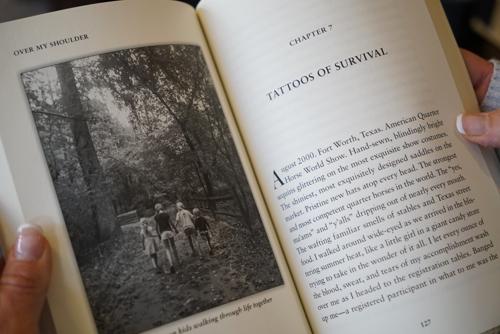 In this Wednesday, March 27, 2019, photo, Kacey Ruegsegger Johnson looks at a photo of her children in a galley copy of her new memoir at her home in