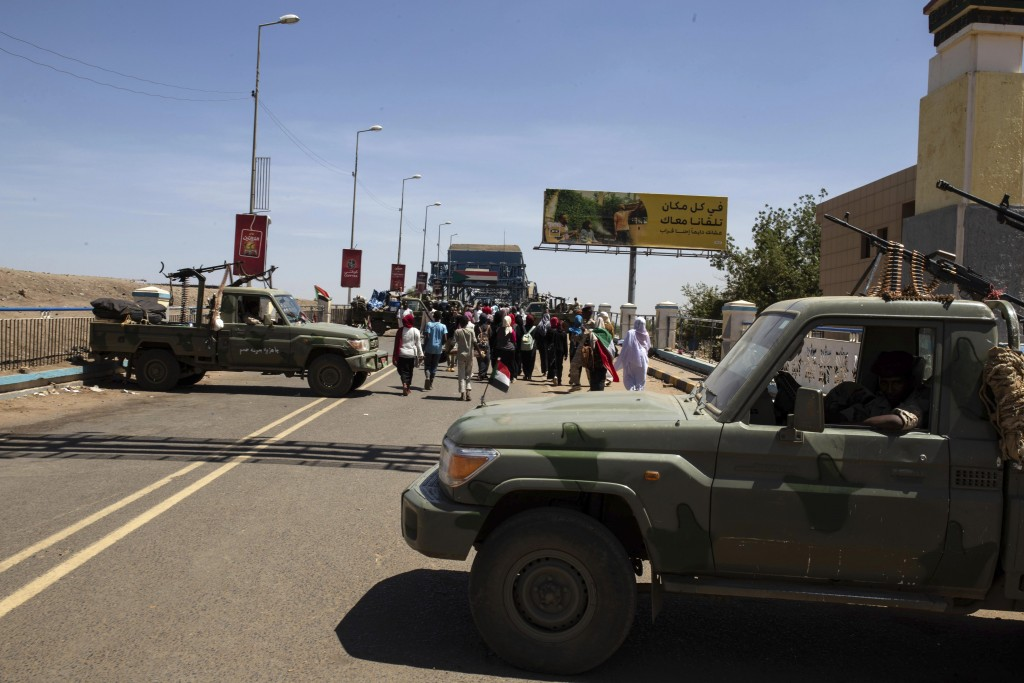 Demonstrators walk past army vehicles protecting the entrance to a rally near the military headquarters in Khartoum, Sudan, Monday, April 15, 2019. Th