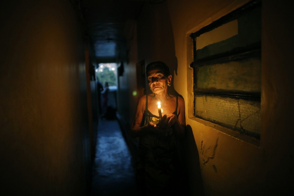 """FILE - In this March 14, 2019 file photo, 72-year-old Elizabeth Guzman Espitia navigates a narrow passages up to her windowless room she calls her """"li"""