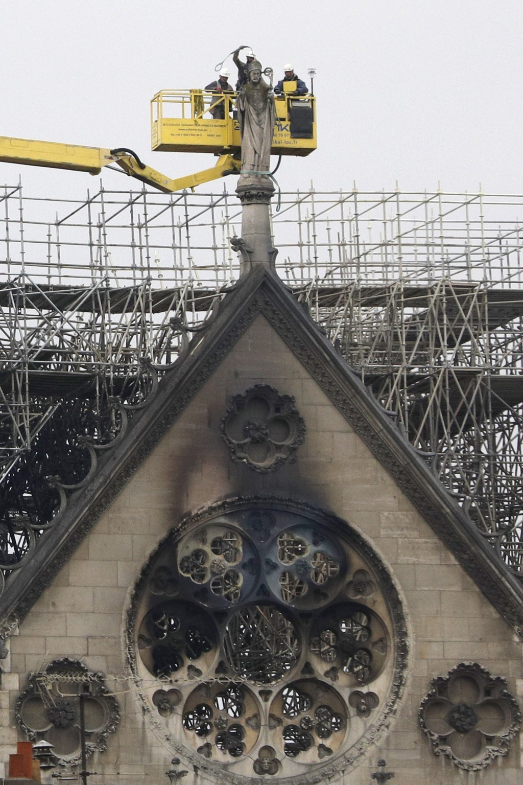 Experts prepare to lift a statue from the damaged Notre Dame cathedral after the fire in Paris, Tuesday, April 16, 2019. Experts are assessing the bla