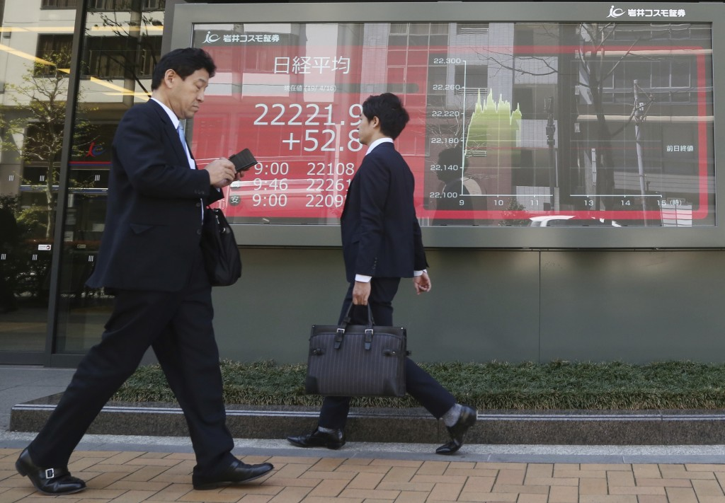 People walk by an electronic stock board of a securities firm in Tokyo, Tuesday, April 16, 2019. Shares were mixed Tuesday in Asia in mostly narrow tr