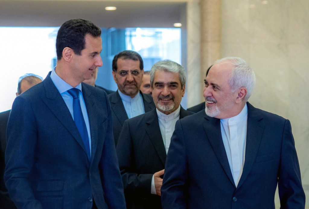This photo released on the official Facebook page of Syrian Presidency shows Syrian President Bashar Assad, left, speaking with Iranian Foreign Minist
