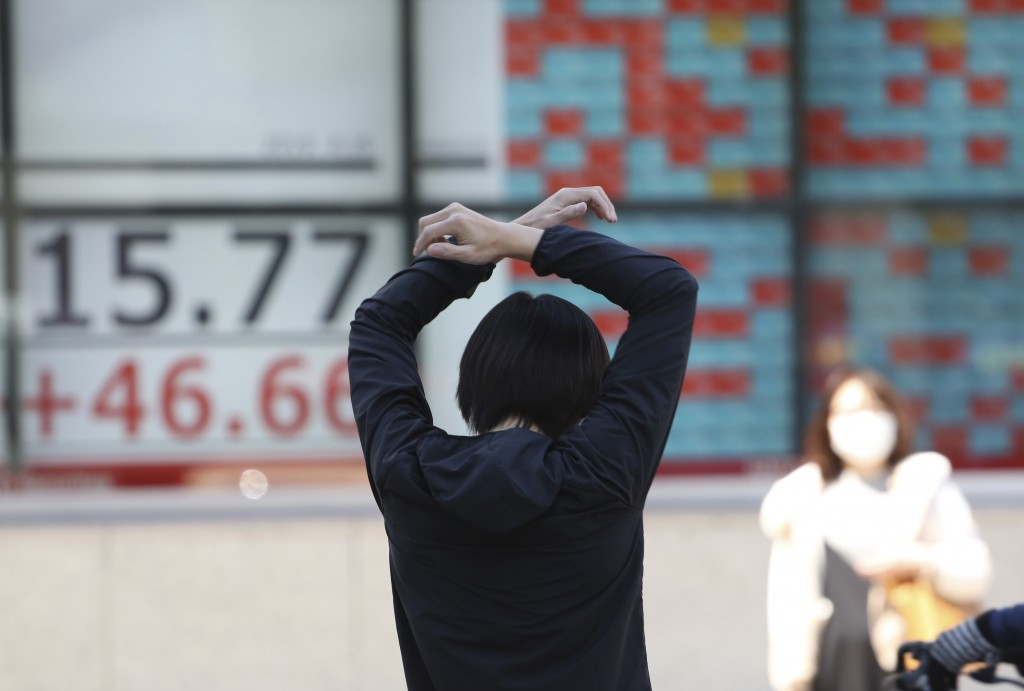 A man stretches in front of an electronic stock board of a securities firm in Tokyo, Tuesday, April 16, 2019.  Shares were mixed Tuesday in Asia in mo