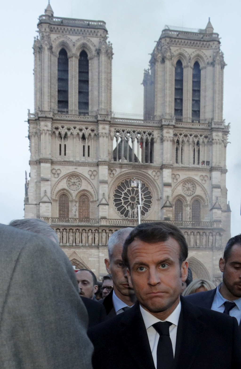 French President Emmanuel Macron walks by Notre Dame Cathedral during his visit to the site in Paris, Monday, April 15, 2019. A catastrophic fire engu
