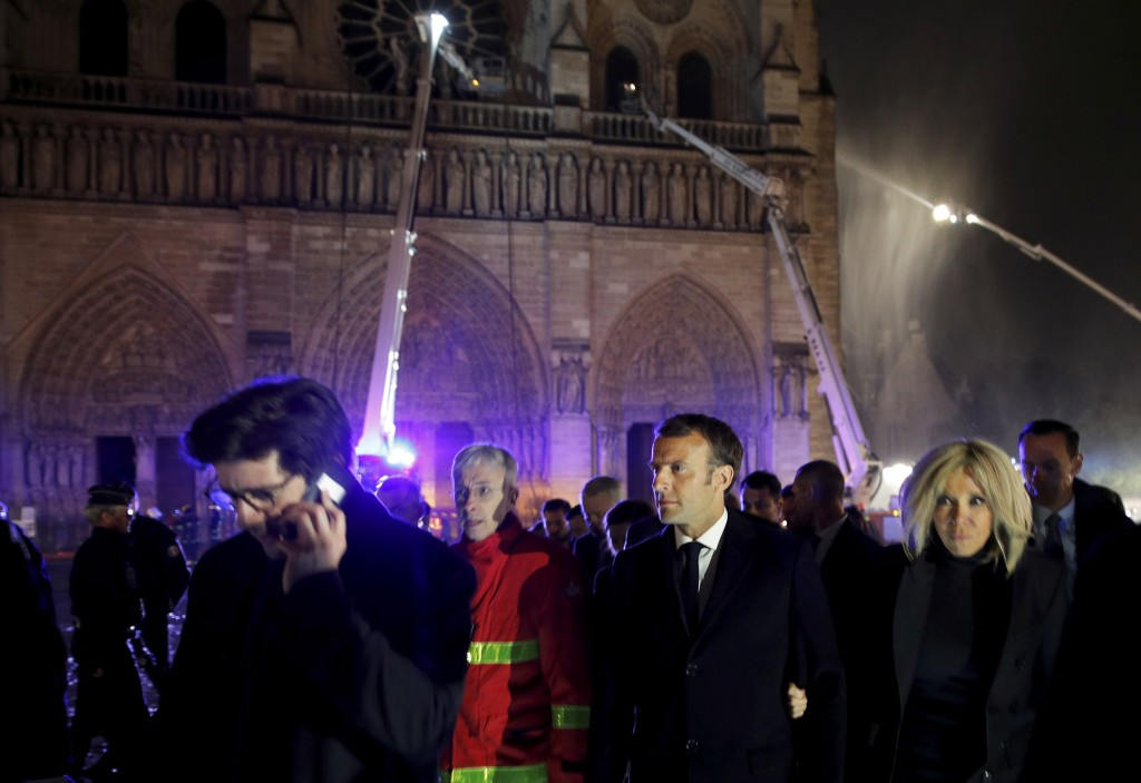 French President Emmanuel Macron, center, and his wife Brigitte walk away from Notre Dame cathedral in Paris, Monday, April 15, 2019. A catastrophic f