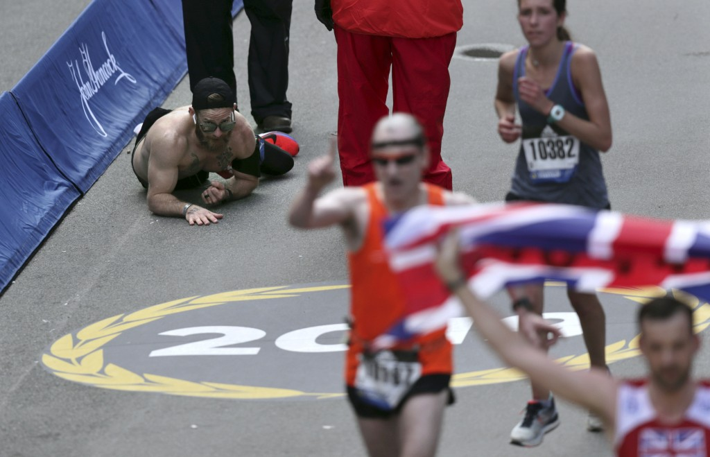 Micah Herndon, of Tallmadge, Ohio, crawls to the finish line in the 123rd Boston Marathon on Monday, April 15, 2019, in Boston. (AP Photo/Charles Krup