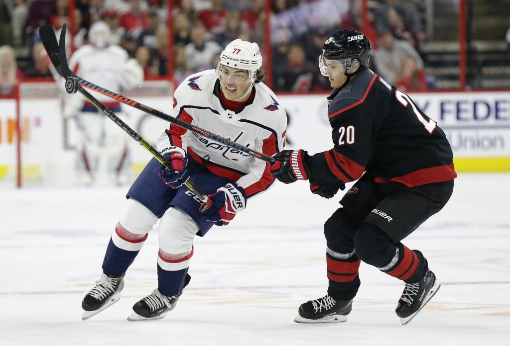 Carolina Hurricanes' Sebastian Aho (20), of Finland, and Washington Capitals' T.J. Oshie (77) chase the puck during the first period of Game 3 of an N