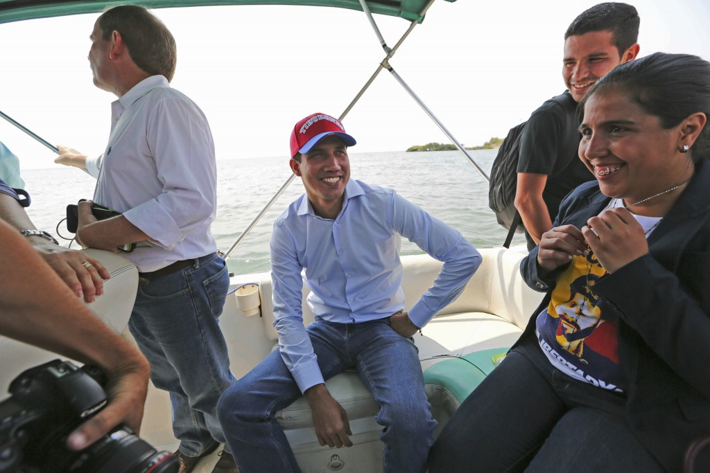 Juan Guaidó, opposition leader and self-proclaimed interim president of Venezuela, sits on a boat with staff members before crossing Maracaibo Lake to
