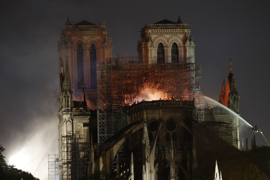 People watch Notre Dame cathedral burning in Paris, Monday, April 15, 2019. A catastrophic fire engulfed the upper reaches of Paris' soaring Notre Dam...