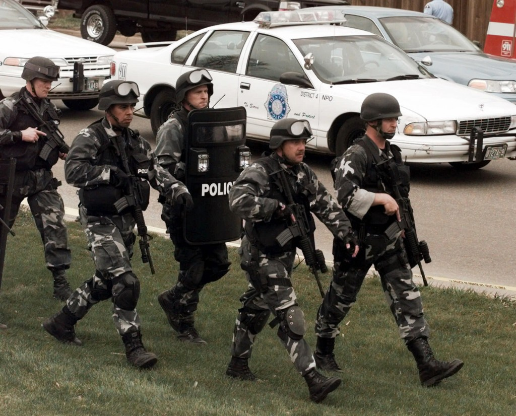 FILE - In this April 20, 1999, file photo, members of a police SWAT team march to Columbine High School in Littleton, Colo., as they prepare to do a f...