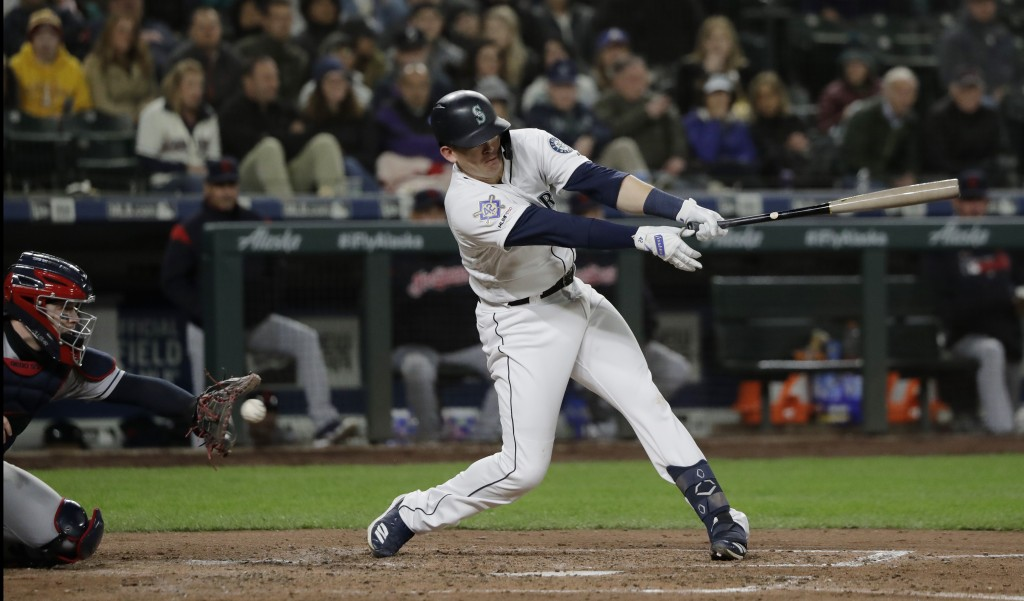 Seattle Mariners' Ryon Healy strikes out swinging with two men on base in the fifth inning of a baseball game against the Cleveland Indians, Monday, A