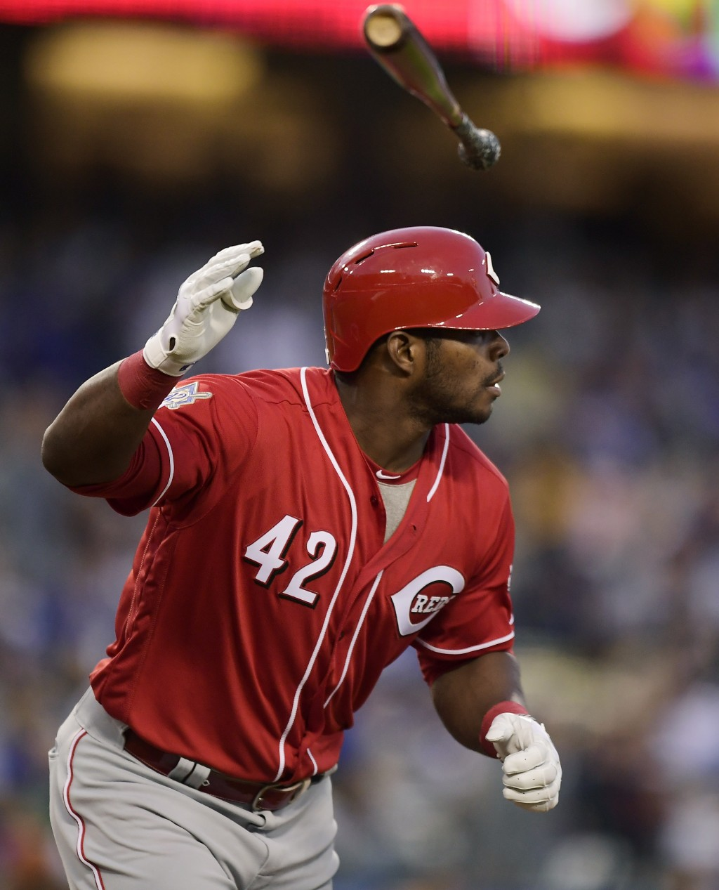 Cincinnati Reds' Yasiel Puig flips his bat after hitting a solo home run during the first inning of a baseball game against the Los Angeles Dodgers, M