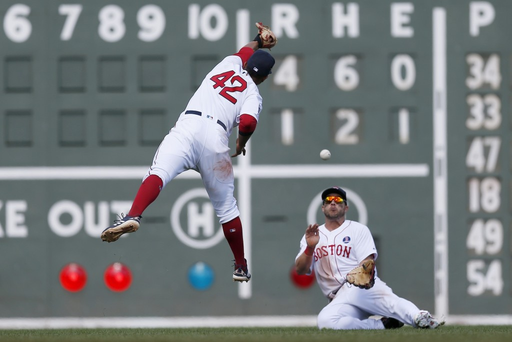 Boston Red Sox's Xander Bogaerts, left, leaps for the ball as Steve Pearce makes the catch on the fly out by Baltimore Orioles' Cedric Mullins during