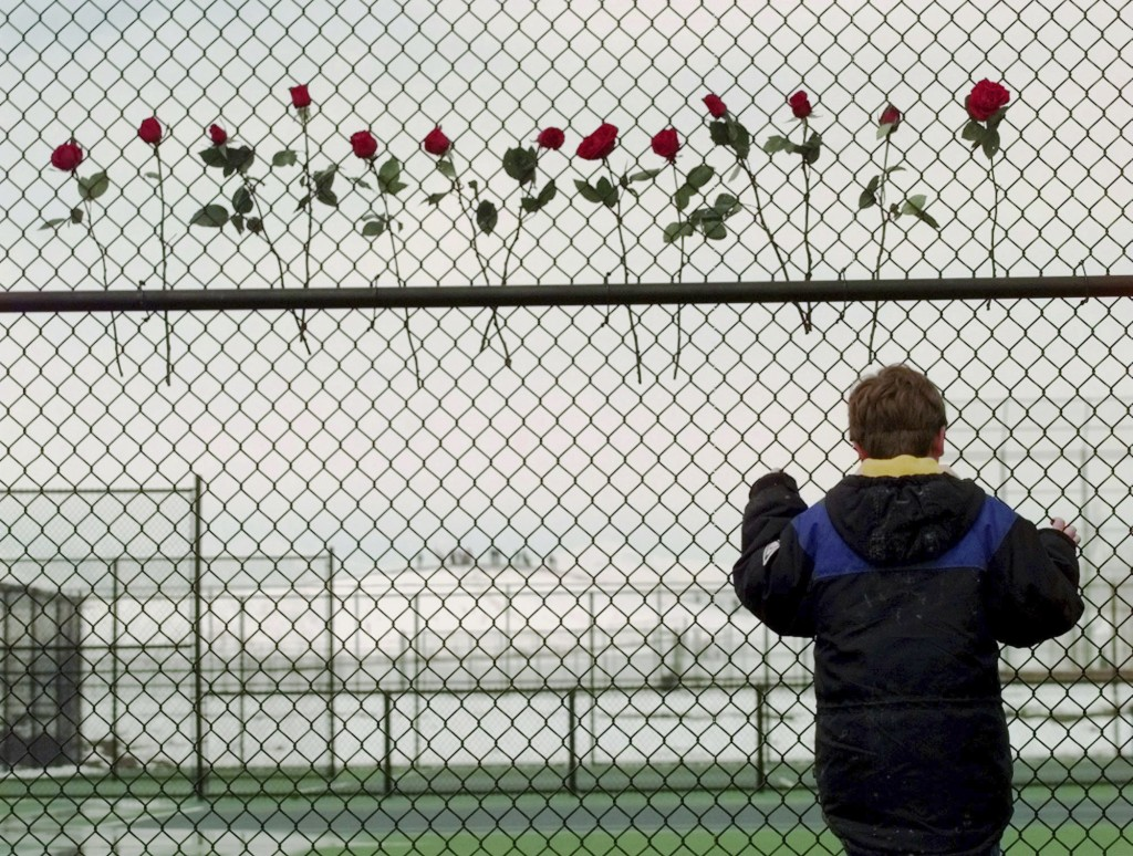 FILE - In this April 24, 1999, file photo, a boy looks through the fence at the Columbine High School tennis courts in Littleton, Colo. Thirteen roses