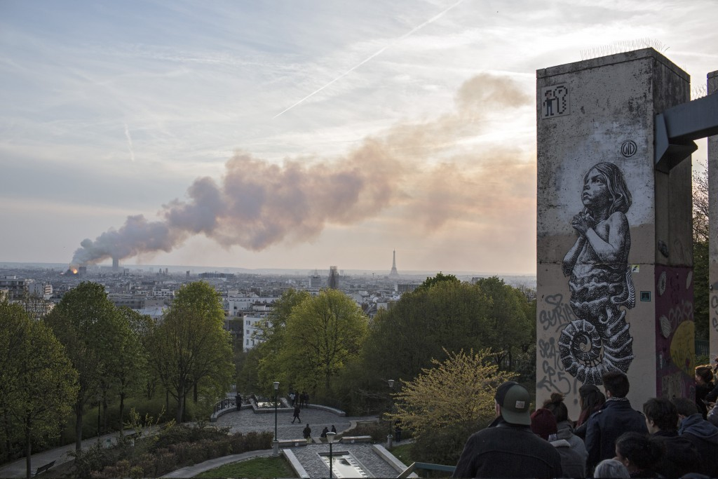 People watch Notre Dame cathedral burning in Paris, Monday, April 15, 2019. Massive plumes of yellow brown smoke is filling the air above Notre Dame C