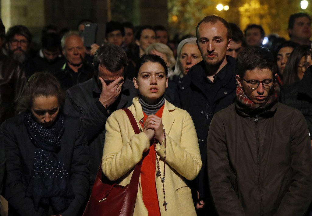 People pray as Notre Dame cathedral burns in Paris, Monday, April 15, 2019. Massive plumes of yellow brown smoke is filling the air above Notre Dame C...