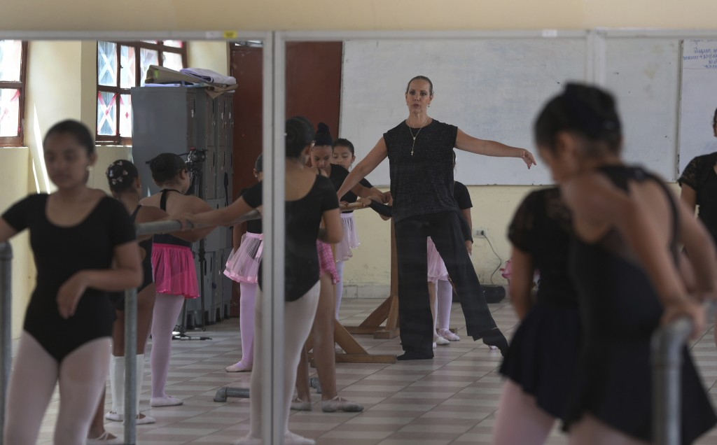 In this April 2, 2019 photo, Maria del Carmen Silva, a former professional dancer, instructs a group of young dancers in a studio at a public school i
