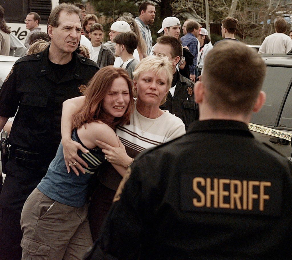 FILE - In this April, 20, 1999, file photo, a woman embraces her daughter after they were reunited following a shooting at Columbine High School in Li