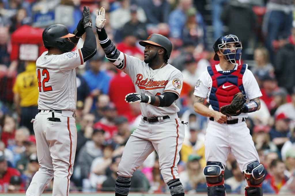 Baltimore Orioles' Dwight Smith, center, celebrates his two-run home run that also drove in Jonathan Villar, left, as Boston Red Sox catcher Blake Swi