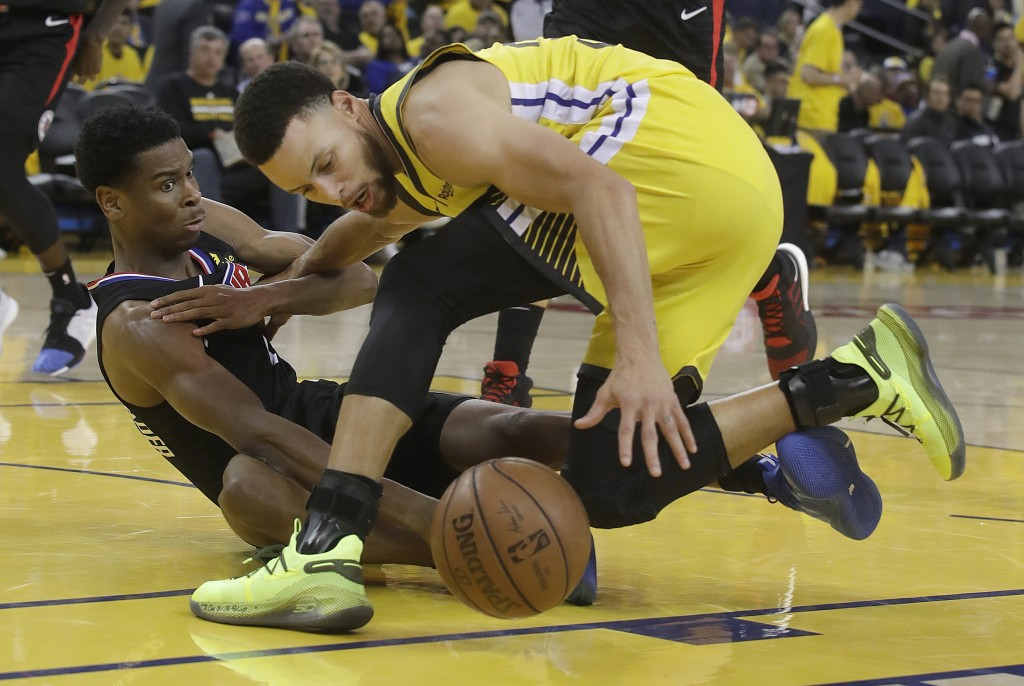 Los Angeles Clippers guard Shai Gilgeous-Alexander, left, and Golden State Warriors guard Stephen Curry reach for the ball during the second half of G...