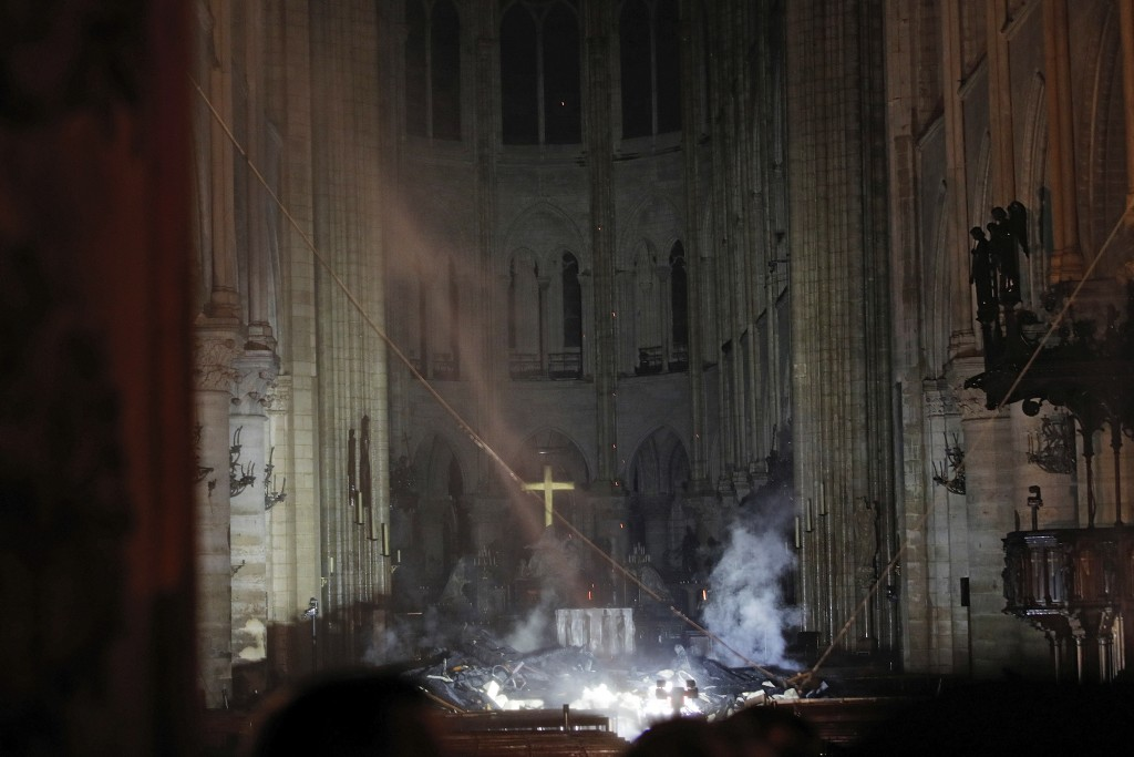Smoke is seen in the interior of Notre Dame cathedral in Paris, Monday, April 15, 2019. A catastrophic fire engulfed the upper reaches of Paris' soari...
