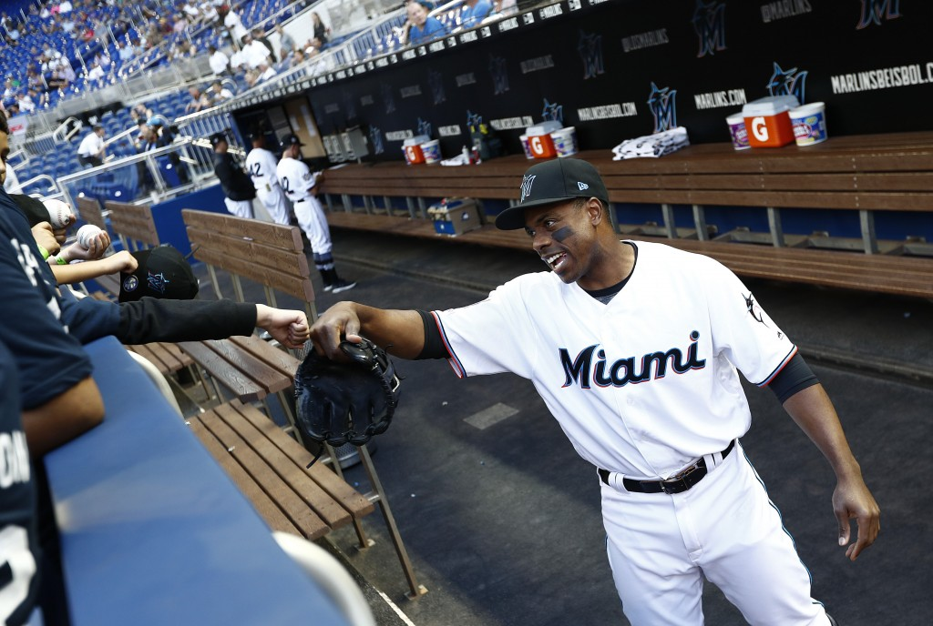 Miami Marlins left fielder Curtis Granderson laughs with a young fan before a baseball game against the Chicago Cubs, Monday, April 15, 2019, in Miami