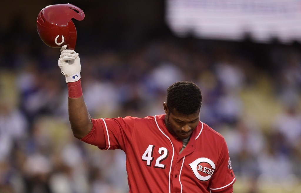 Cincinnati Reds' Yasiel Puig tips his helmet to fans as he comes up to bat during the first inning of a baseball game against the Los Angeles Dodgers,