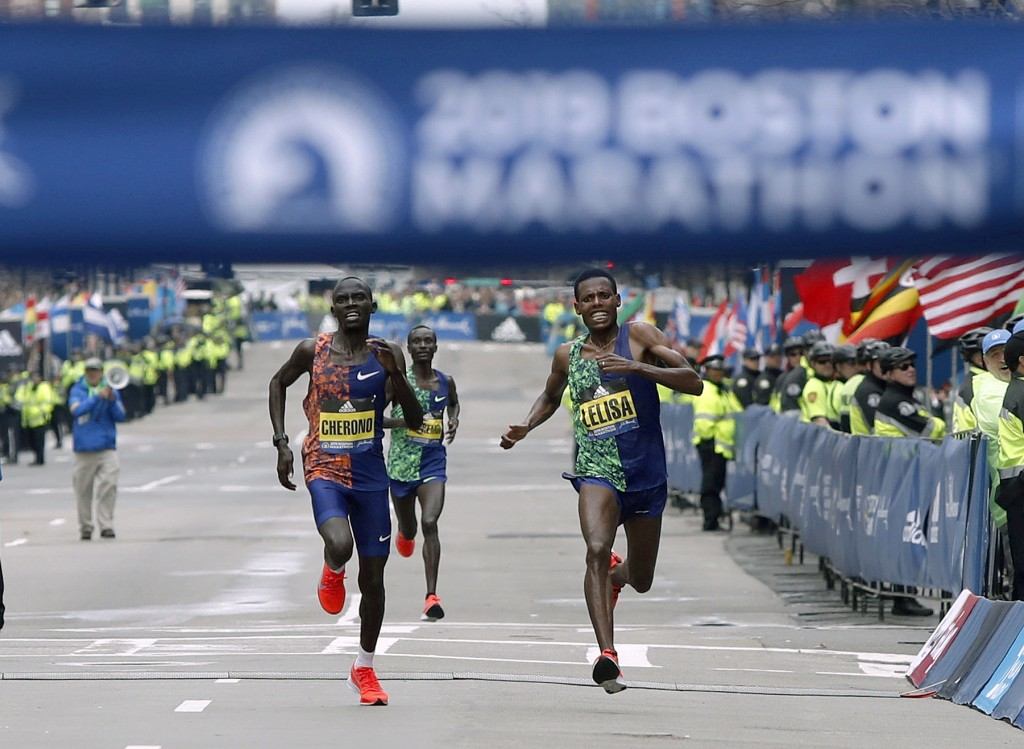 Lawrence Cherono, left, of Kenya, runs to the finish line to win the 123rd Boston Marathon in front of Lelisa Desisa, of Ethiopia, right, on Monday, A
