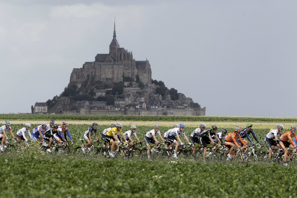 FILE - In this Thursday July 7, 2011 file photo, the pelaton passes the world heritage site Mont Saint-Michel, a rocky tidal island which holds a mona
