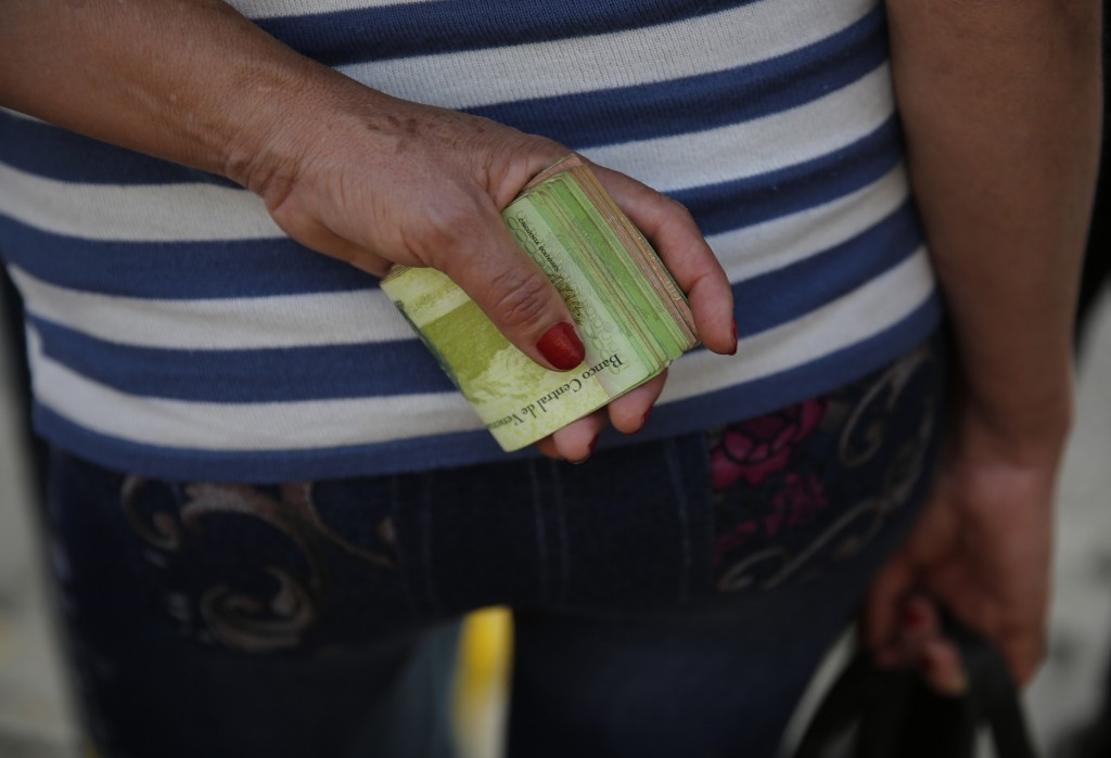 FILE - In this Feb. 7, 2018 file photo, a woman holds a large wad of bills to pay her bus fare in Caracas, Venezuela. Hyperinflation has slashed many