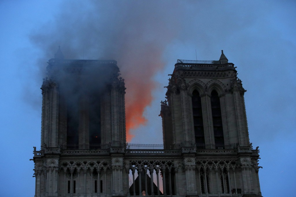 Smoke and flames fill the sky as a fire burns at the Notre Dame Cathedral during the visit by French President Emmanuel Macron in Paris, Monday, April