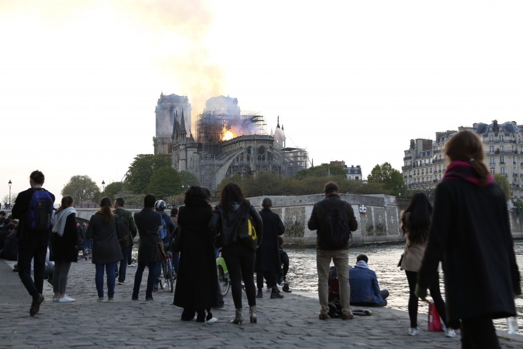 People standing on the banks of the river Seine watch as flames and smoke rise from Notre Dame cathedral as it burns in Paris, Monday, April 15, 2019.