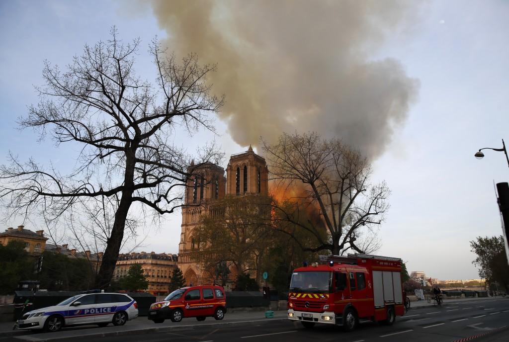 A polcie car and fire brigade vehicles park while Notre Dame cathedral is burning in Paris, Monday, April 15, 2019. Massive plumes of yellow brown smo