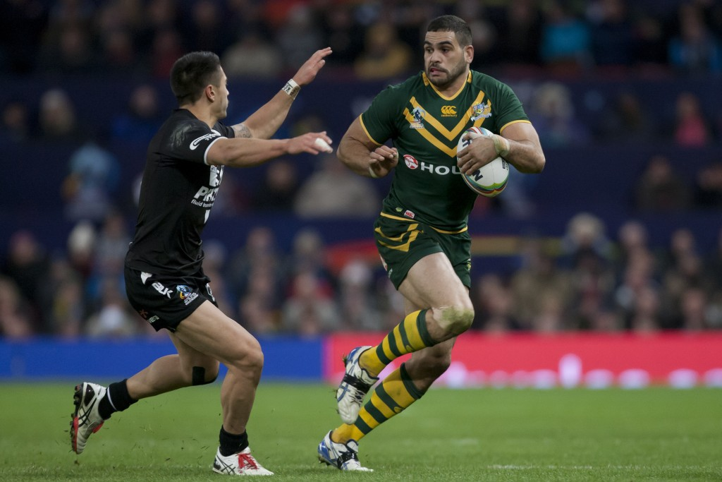 FILE - In this Nov. 30, 2013, file photo, Australia's Greg Inglis, right, keeps the ball from New Zealand's Shaun Johnson during their World Cup Final...
