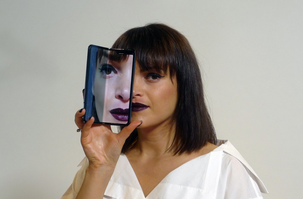 A model holds a Samsung Galaxy Fold smartphone to her face, during a media preview event in London, Tuesday April 16, 2019.  Samsung is hoping the inn
