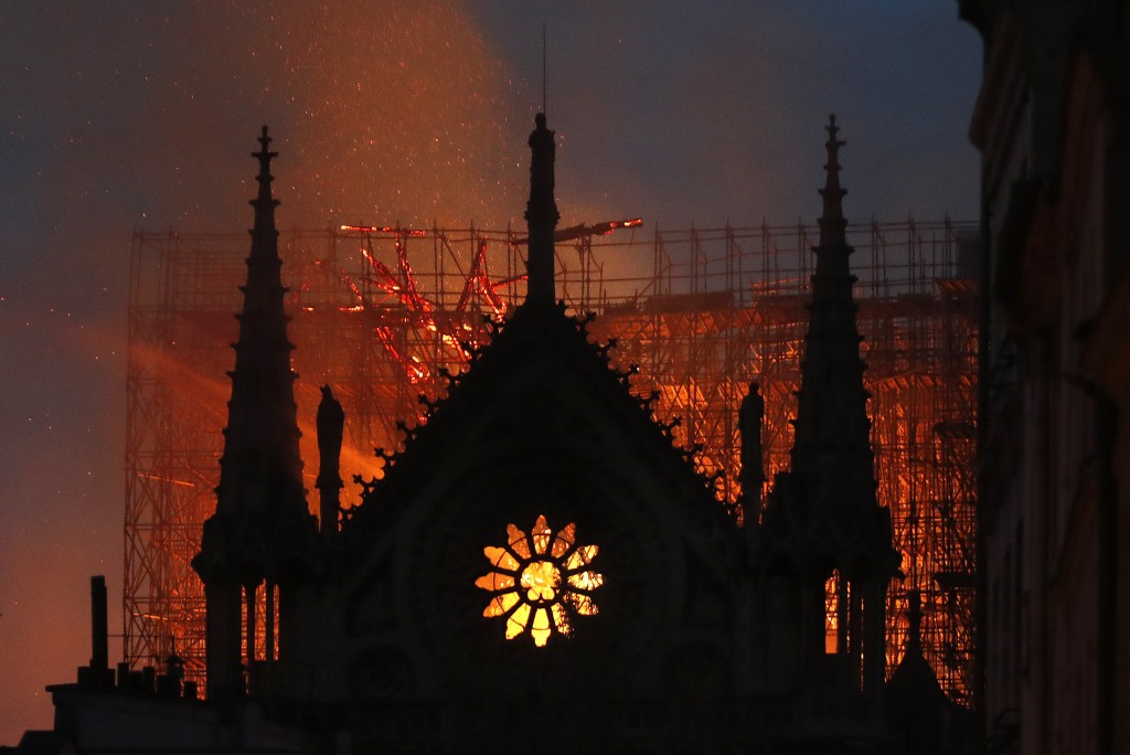Flames and smoke rise from Notre Dame cathedral as it burns in Paris, Monday, April 15, 2019. Massive plumes of yellow brown smoke is filling the air ...