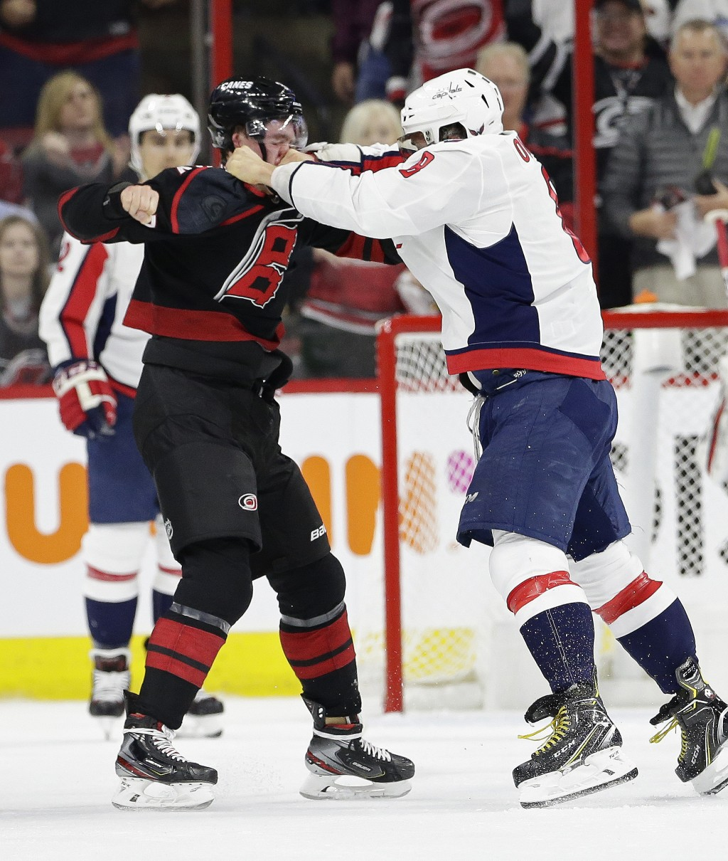 Washington Capitals' Alex Ovechkin, right, of Russia, punches Carolina Hurricanes' Andrei Svechnikov, also of Russia, during the first period of Game