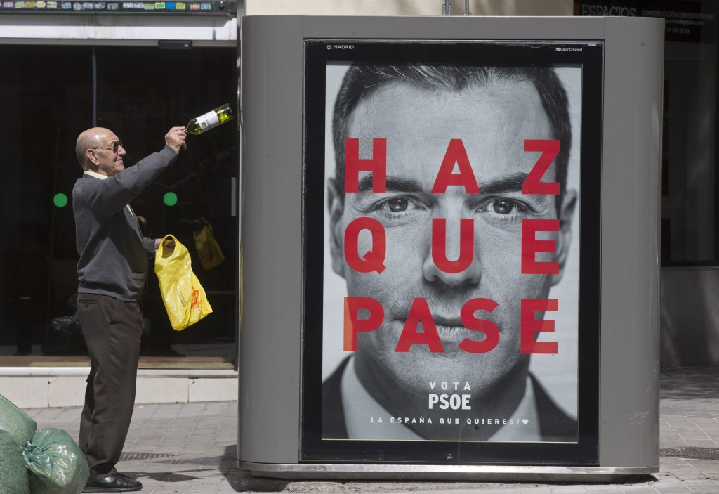 A man disposes of an empty bottle into a recycling container with an election poster showing the face of Socialist prime minister Pedro Sanchez in Mad